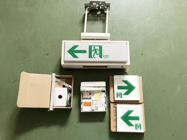 上:耐用年数を過ぎた避難誘導灯 下:交換する新品の避難誘導灯