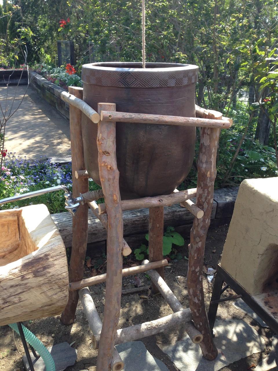 雨水タンク。古い水がめを利用して、タープに降った雨が集まります。