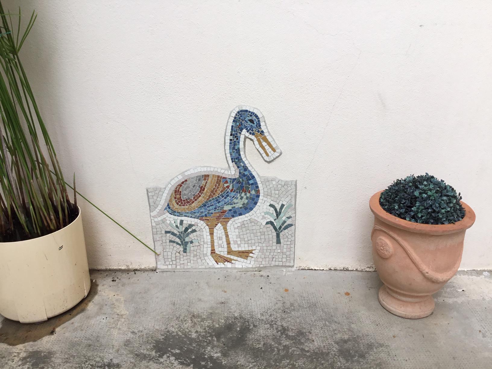 sur un mur de sa maison, un canard en grès cérame,