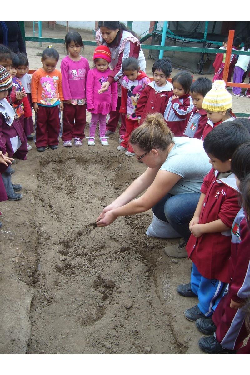 . Nuestra amiga voluntaria Fabiola les enseña como coger los nutrientes y luego ponerlos en el suelo.