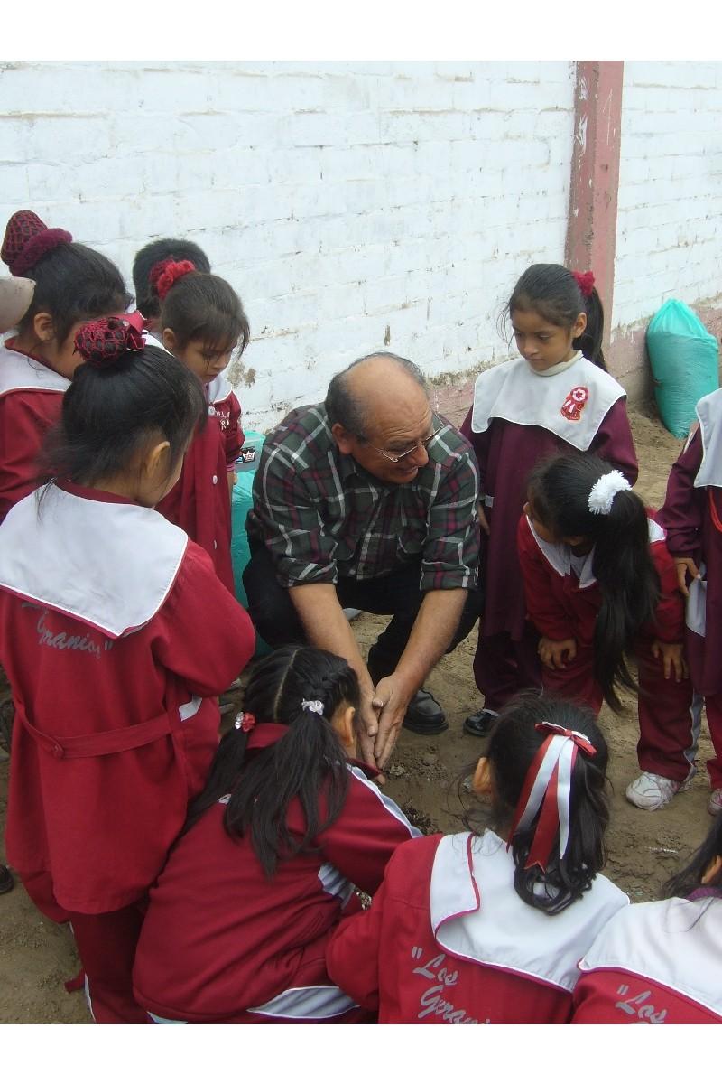 El Prof. Héctor les muestra como echar los nutrientes al suelo.
