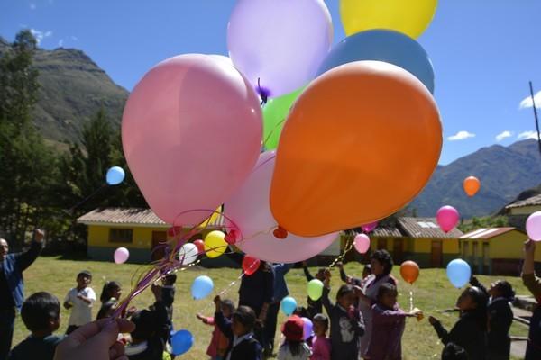 Salen al patio y emocionados se preparan para soltar sus globos.