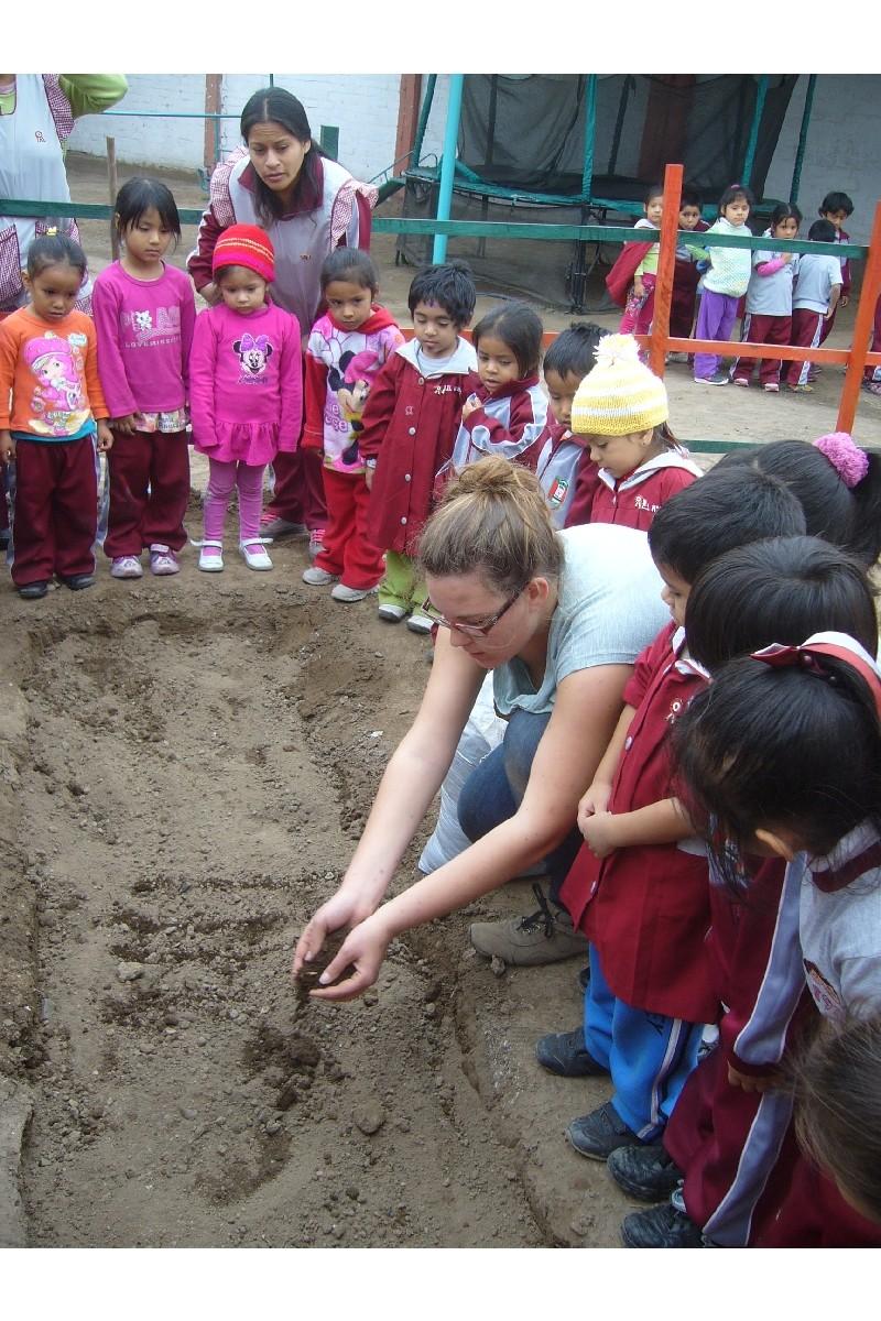 Nuestra amiga voluntaria Fabiola les enseña como coger los nutrientes y luego ponerlos en el suelo.