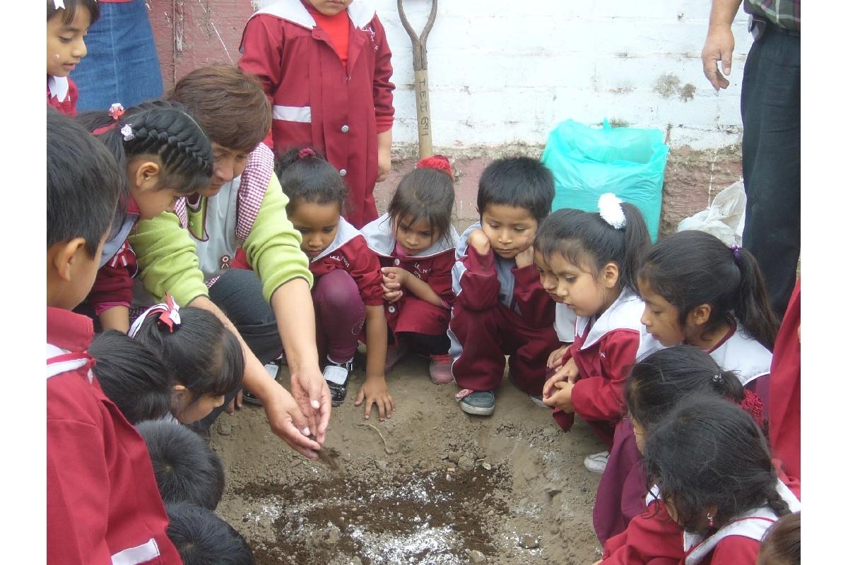 La Directora les muestra como echar los nutrientes al suelo.