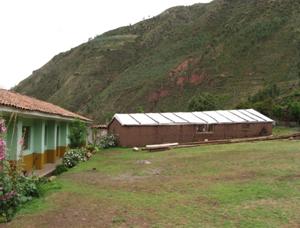 La escuela pública de la localidad de Pacor, a la derecha el gran invernadero de su Biohuerto Educativo (Cusco - Perú)