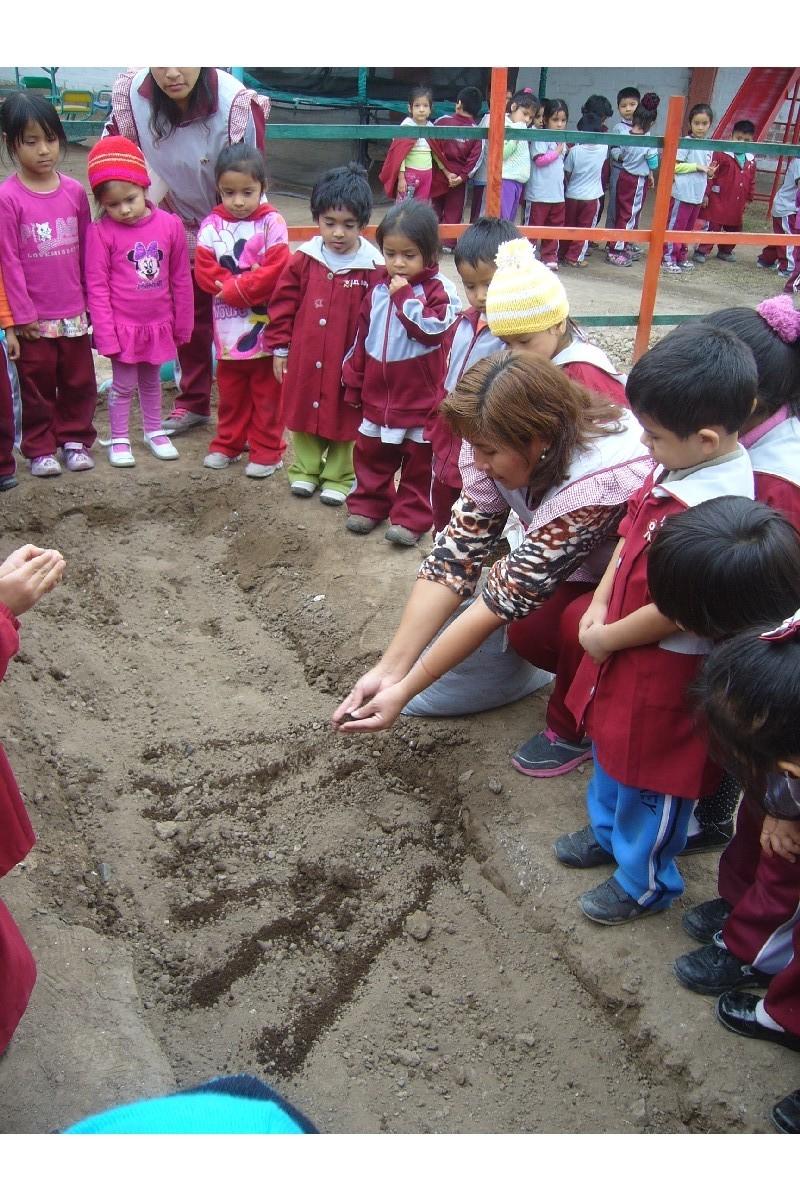 La profesora muestra como echar los nutrientes al suelo.