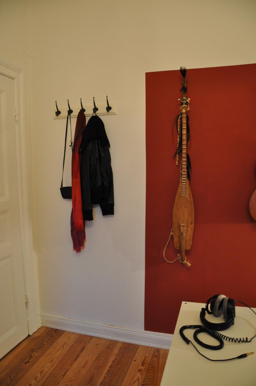 WG-ZIMMER HH | Garderobe verschwindet hinter der Eingangstür | Blickfang eingerahmte Gitarren
