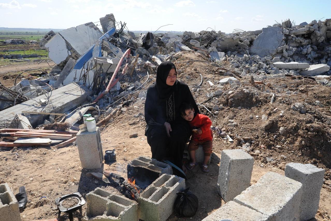 2008年暮れのガザ猛攻。破壊された自宅の前で座り込む母子。このたきびだけが二人の財産である。
