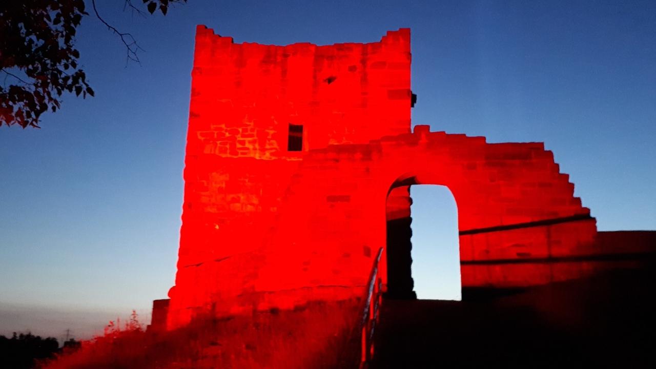 Burgruine erstrahlt in rotem Licht