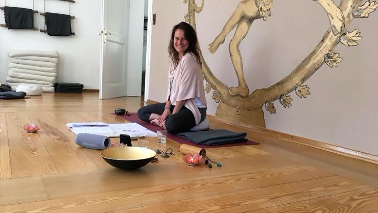 Simone Sauer im Yoga-Sitz auf einem Holzboden in einem Yoga-Raum.