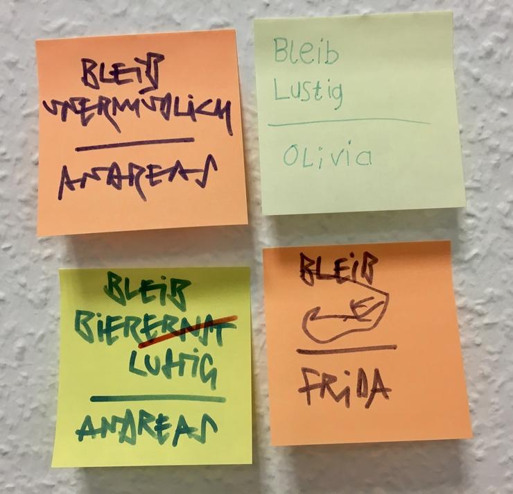 4 Post-its auf einer Wand mit Rauhfasertapete. Auf den Post-its steht: Bleib lustig, bleib vergnüglich, bleib biererst bzw. bier lustig (Ernst ist durchgesrichen) Unterschrieben sind die Bortschaften von Andresas, Olivia und Frida