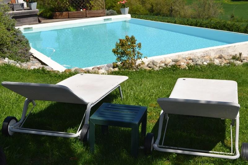 Des lits bains de soleil sont disposés en bord de piscine pour profiter du soleil ou pour une sieste à l'ombre des pins