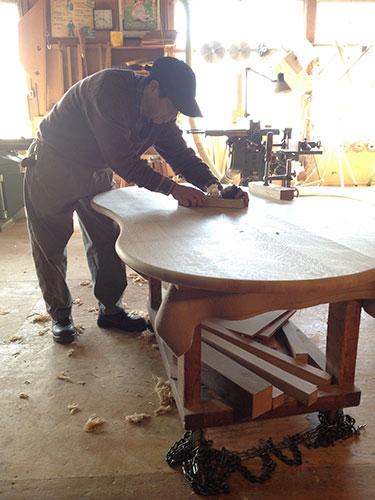 """ビーンズダイニングテーブルの表面に鉋目をほどこす。職人は鉋の研ぎ具合と""""歯""""の出具合をよく確かめながら作業を行います。"""