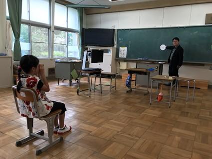 愛知県の小学校で弱視の児童の指導を行なっている様子。弱視にとって見やすい環境を構築することが、我が研究室でのテーマの一つです。見えにくさを抱える児童生徒が通う学校から、来校しての指導を依頼されることも多くあります。この写真のように直接指導をすることもあります。この写真は、小学校で学ぶ見えにくさのある小学生が遠くを大きくして見るための道具(単眼鏡)の操作を習得する方法を直接指導し、学校での日々の指導に生かすために、その様子を担任の先生がご覧になっている様子です。