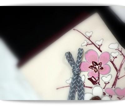焦げ茶の無地紬に梅の花を描いた白地の染め帯を合わせています。森口華弘さんの作品です。白い花がハートにも見えます。