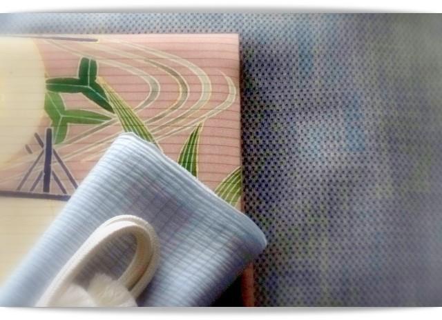 きものはブルー地蚊絣の夏塩沢。帯は久呂田明功作染め帯。流水・帆掛け船・オモダカ・水草などが描かれている。