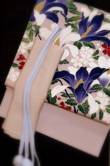 藤色の鬼しぼ縮緬に、白木蓮・紫木蓮・桜など春の花を描いた染め袋帯です。