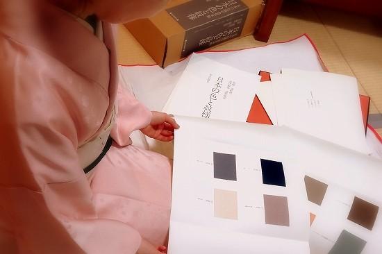浦野理一「日本の色と文様」に収められた色見本から、お気に入りを探す生徒さんの姿。ピンクのきものがお似合いです。