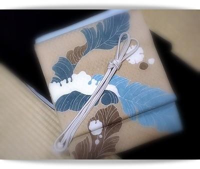 焦茶色の無地紬に、品川恭子作雪持ち芭蕉の帯。白い帯締めで春待つ心を…。