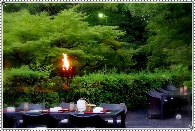 かがり火が焚かれ、テーブルがセッティングされた、緑滴る太閤園のお庭です。