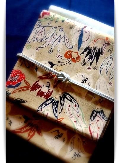 ベージュの紬地に蝶や花々を描いた型絵染の帯。板倉眞理子作。きものは藍地の綿薩摩。