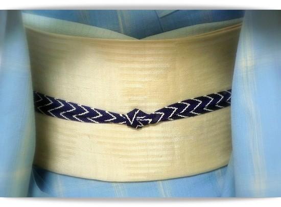 爽やかなブルー地にベージュの格子柄のきものは、駒生布と呼ばれる織物です。青海波を織りだした白地の帯は池田リサさんの作品です。着付けのお稽古に。