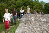 Eine Gruppe erkundet die Burg und läuft auf einem Weg der Ruine entlang.
