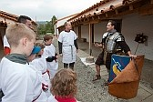 Kinder, als Legionäre verkleidet, hören einem Offizier zu.