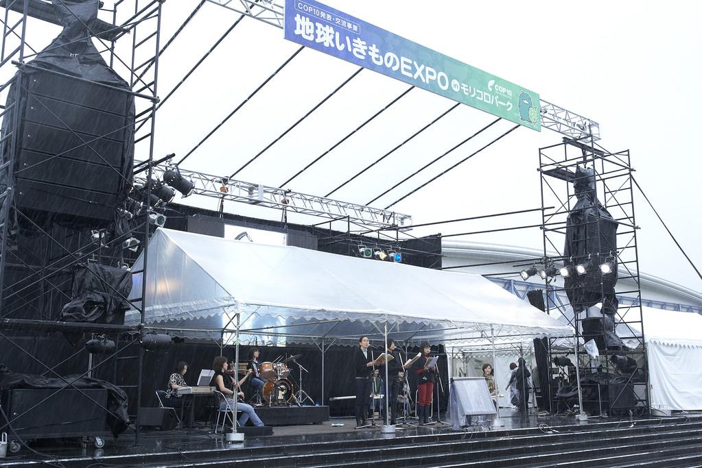雨よけテントの下で超リアル「雨ニモマケズ」、パロル舎・小林敏也氏の画本を映したLEDビジョンが見えにくく、残念…