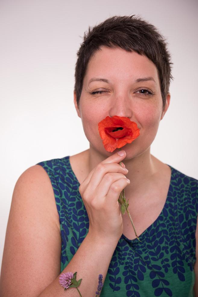 Bild Foto Frau jung Portrait Blume Blumenkind Flowerpower Powerfrau zwinkern ICHwerkstatt momentissimo Fotografin Barbara Wagner Mohnblume Kraft Beratung