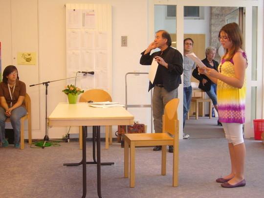 Mehmet Kilic lud Darlin Bachman an das Pult ein. Darlin trug die Textvorlagen und die Aufgaben vor, damit das Publikum weiß, worauf die Texte der jungen Autorinnen und Autoren basieren.