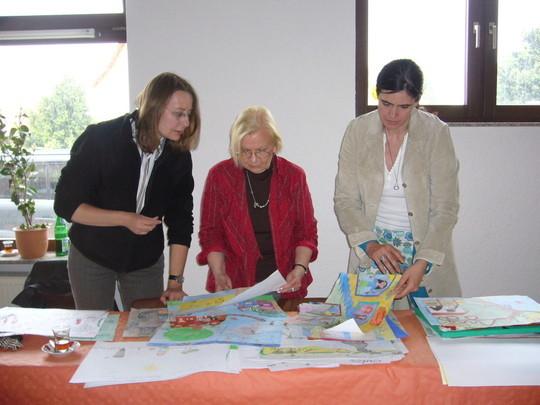 Kulturdezernentin Andrea Manz, Kunstlehrerin Marieluise von Schuckman und Lehrerin Yvette Gatzer vergleichen die Bilder miteinander.