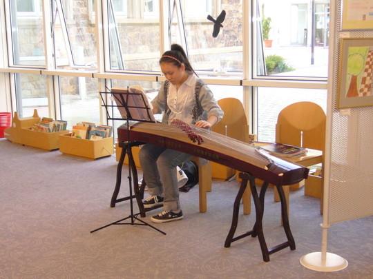 """Mailin, eine junge chinesische Musikerin, machte an ihrem Instrument """"Guzheng"""" die musikalische Einführung."""