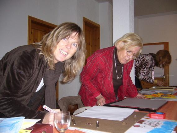 Kerstin Schäffken, Marieluise von Schuckmann und Maria Kaufmann sind dabei mit anderen anwesenden gemeinsam die Bilder einzurahmen.
