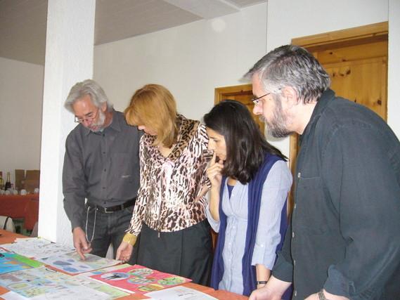 Zwei Kunstlehrer, eine Kunstlehrerin der ADS-Hargesheim und  Maria Kaufmann sortieren die Bilder.