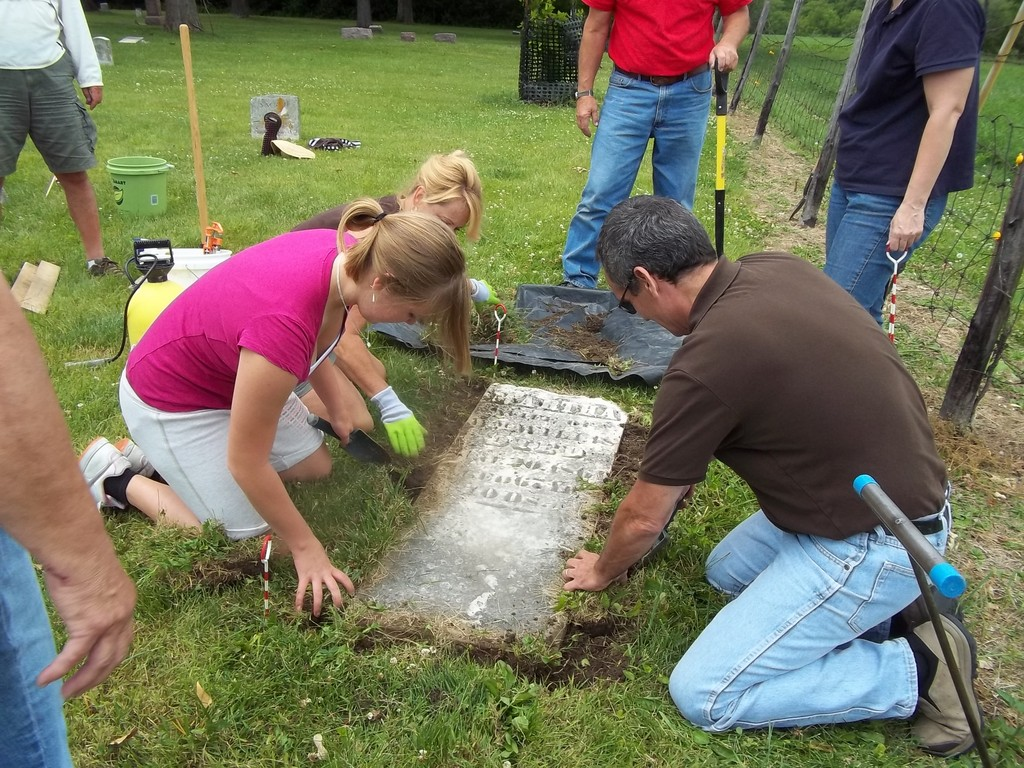 Workshop participants expose and excavate a headstone at the Old Macomb Cemetery.
