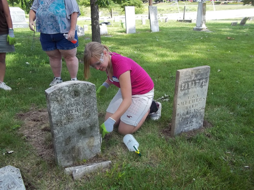 Cheyenne Chalkus, a Girl Scout from Salem, IL, cleans the marker for Thomas Smithers, a veteran of the War of 1812.