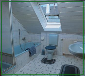 Hellblaues Komfortbad mit Wanne/Dusche/WC, Waschbecken mit Ablage und Kosmetikspielgel.