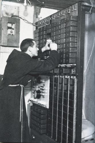 Un religioso mentre ripara un quadro elettrico