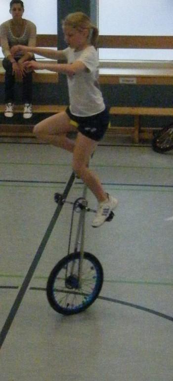 Einbein auf Hochrad, rechtes Bein an Stange