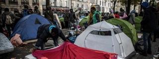 8.パリ19区、高架鉄道下の中央帯空き地を利用して生活する難民。両脇道路のカフェや商店にパリ市民が近寄らなくなって、店は倒産寸前。