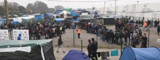 4.ボランティアによる、毎日昼夜2回の食事サービスに並ぶ難民達。手前フェンスの2人は警備ポリス。トイレ前も同じ様な行列で、喧嘩もおきる。