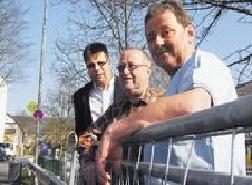 """Die Achenbacher Günther Langer, Karl Scheid und Hans-Peter Weber (von links) ärgern sich seit Jahren über die zweitweise stillgelegte beziehungsweise provisorische Bushaltestelle in der Straße """"Im Samelsfeld""""."""