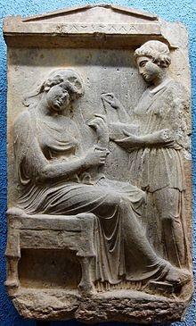 Femme assise ajustant son bracelet pendant que sa jeune esclave ouvre un coffret à bijoux. Stèle funéraire trouvée à Athènes et datant d'environ 430 – 400 avant J.C. Hauteur : 1,35 mètre. Œuvre d'art visible aujourd'hui au British Museum à Londres.