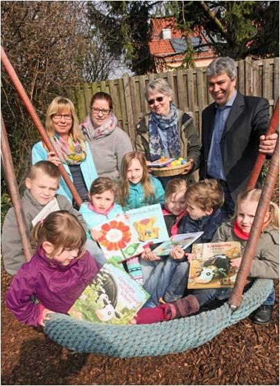 Auch die Frühlingszeit ist Lesezeit – denn Lesen kann man ebenso draußen. Die Kinder und Kindergartenleiterin Ulrike Hollerith nehmen die Bücherspende auf der Nestschaukel aus Händen von Winston Effenberger, Heike Jennewein und Jutta Commichau entgegen.