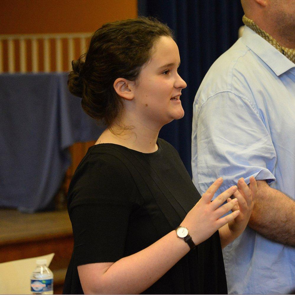 Marie, membre de l'équipe organisatrice, s'adresse au public
