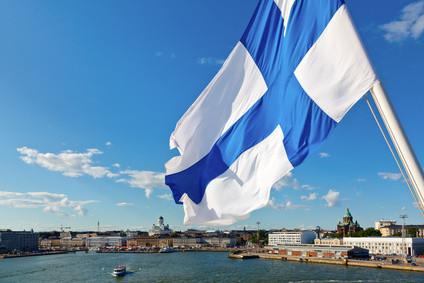 Finnische Flagge vor der Kulisse vom Hafen in Helsinki