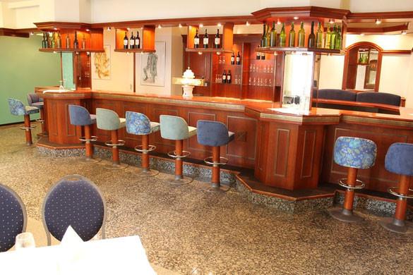 Thekenanlage mit Barhockern und weiteren Sitzplätzen hinter der Theke