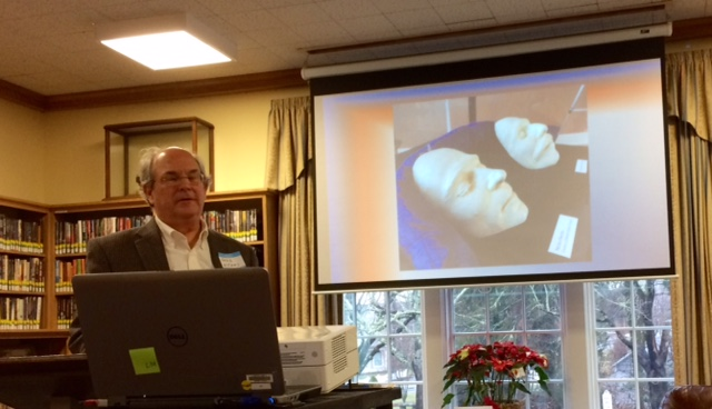 Greg Williams, speaking with death masks of Sacco and Vanzetti in the background at the conclusion of his presentation
