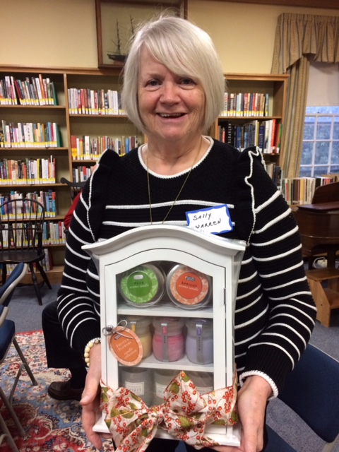 Winner of luncheon drawing of cabinet with candles, Friends' member, Sally Warren.